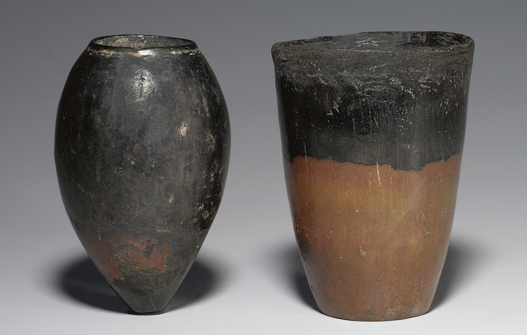 TWO EGYPTIAN BLACK-TOPPED POTT