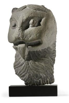 A gray schist head of a lion