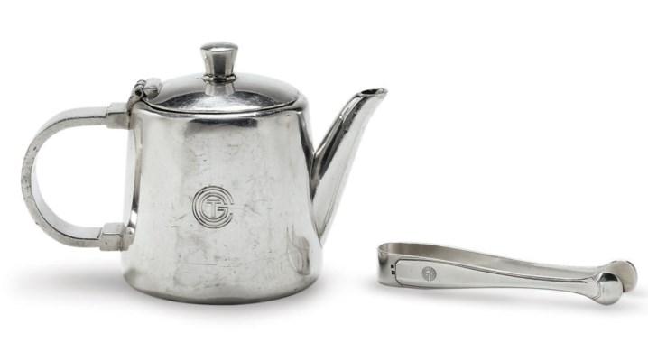 A tea pot and sugar tongs in p
