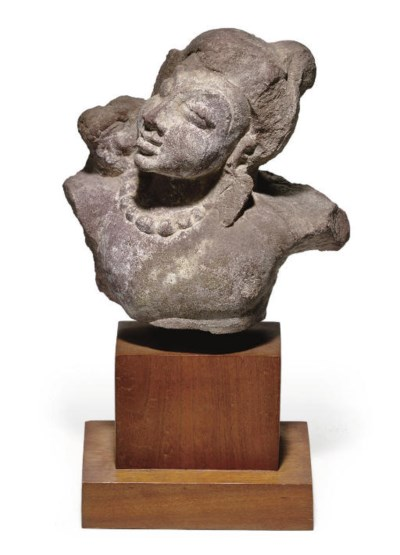 A small red sandstone bust of