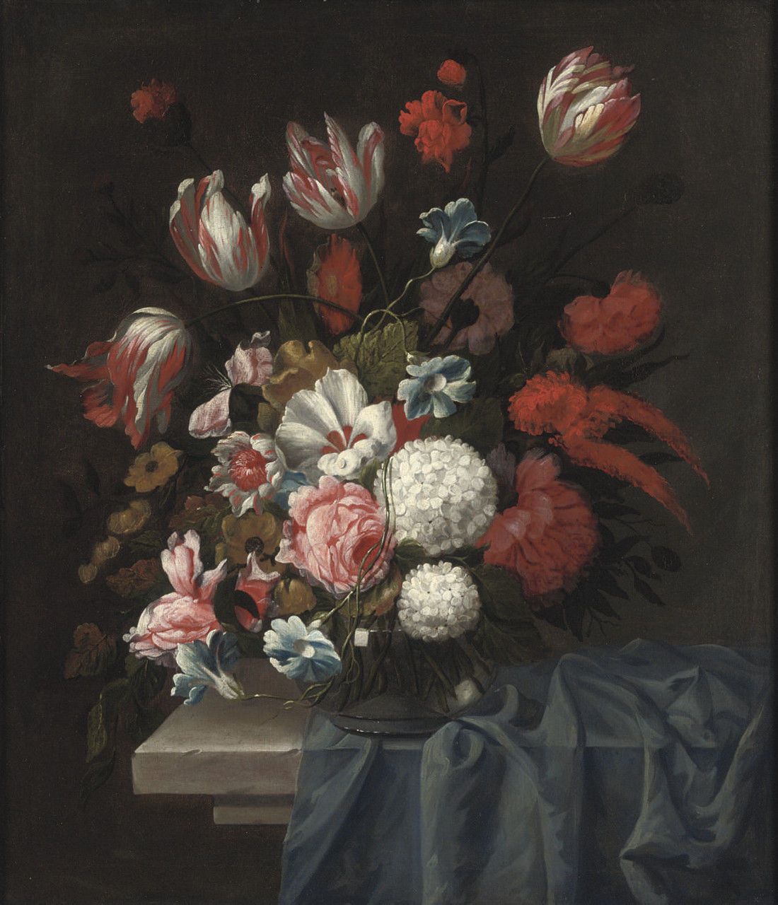 Tulips, roses, poppies and other flowers in a glass vase on a stone table