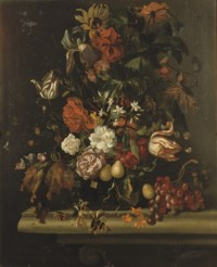 Tulips, irises, carnations and other flowers in a glass vase, together with grapes on a stone ledge