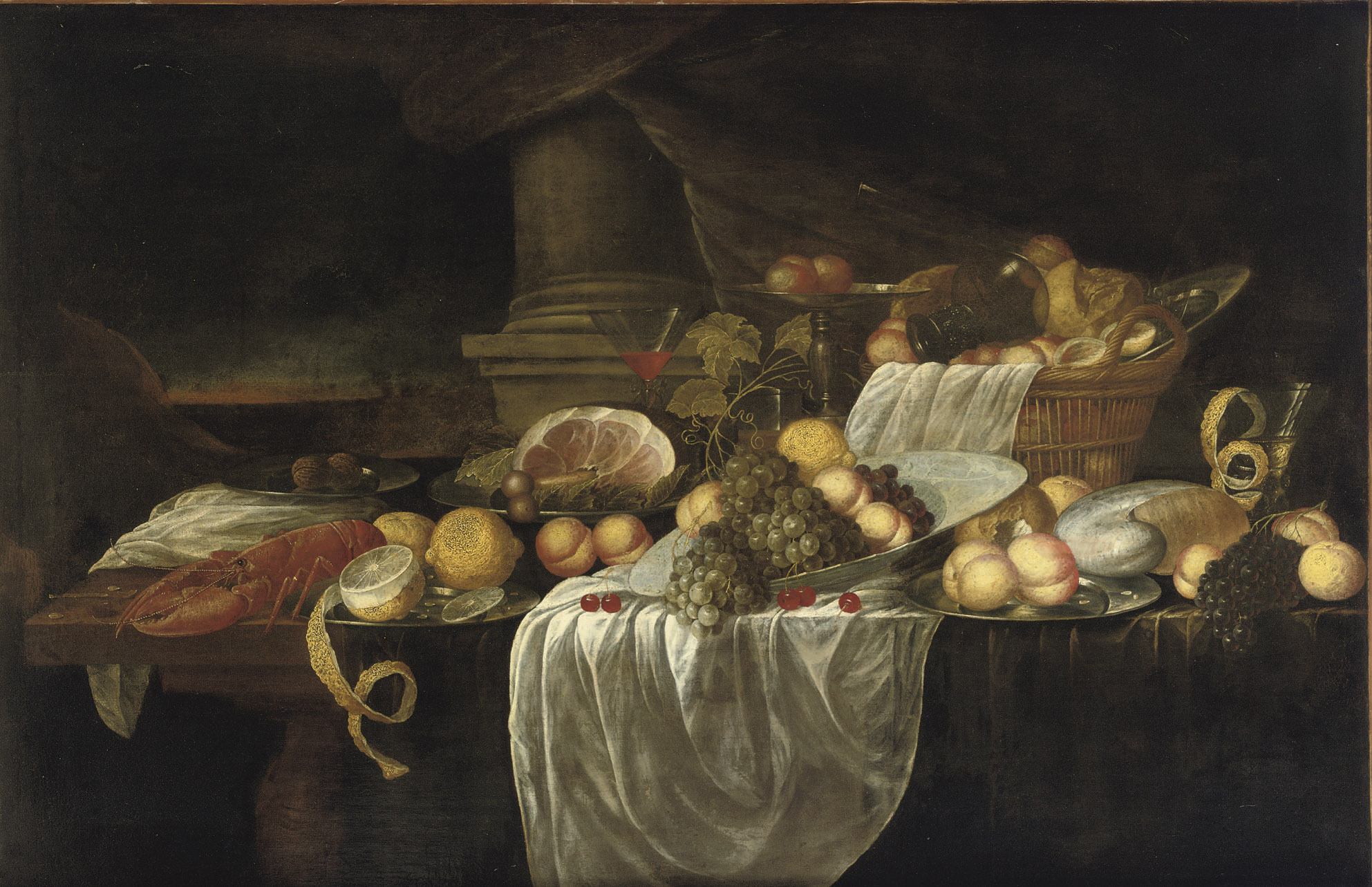 A porcelain bowl with grapes, peaches and lemons together with a wicker basket with bread, a glass, lobster, ham and various other objects all on a partially draped table