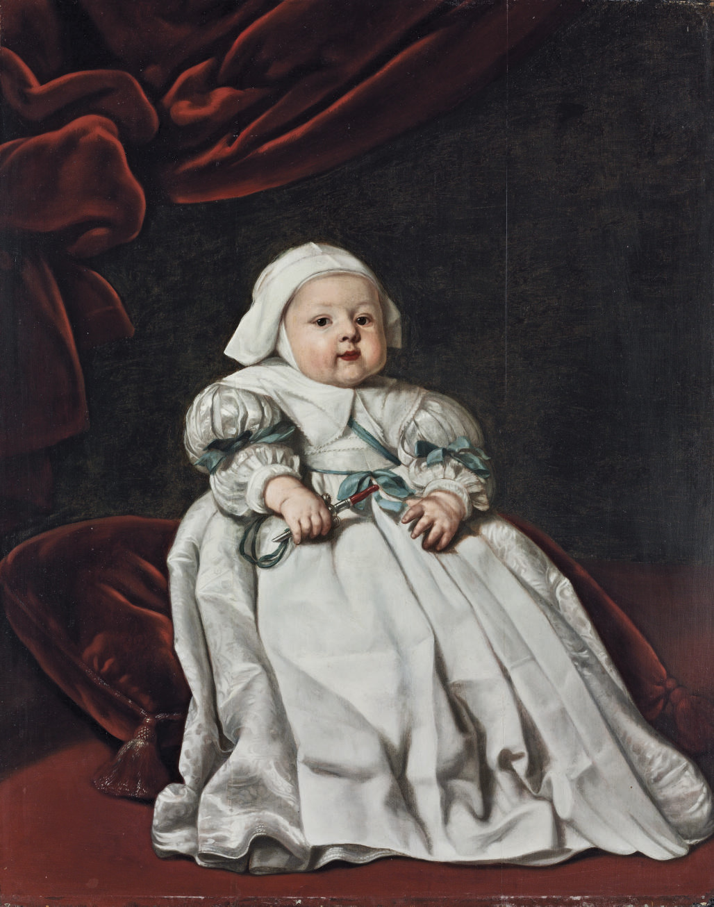 Portrait of a child, full-length, in a white gown and bonnet, holding a jewelled rattle, seated on a red cushion