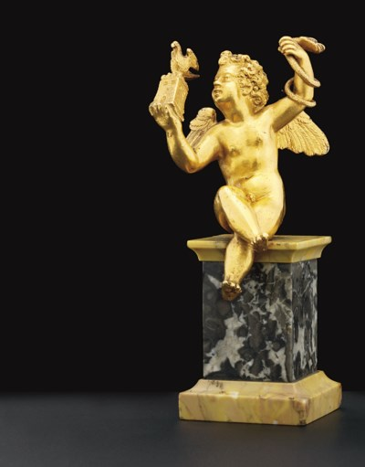 A GOLD FIGURE OF A SEATED PUTT