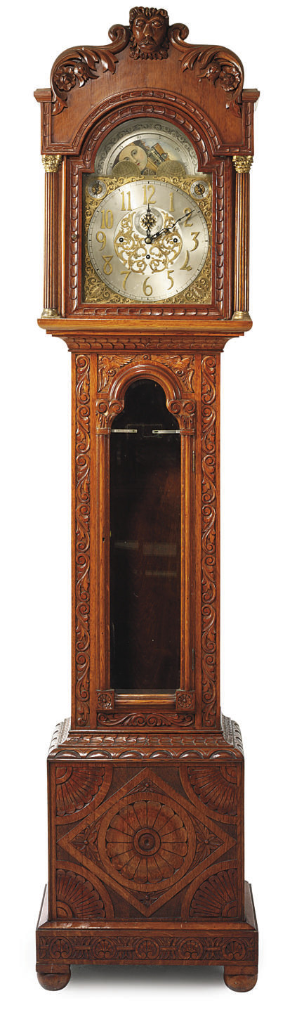 AN EDWARDIAN CARVED OAK QUARTE