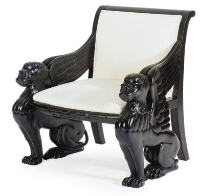 A CARVED AND EBONIZED ARMCHAIR