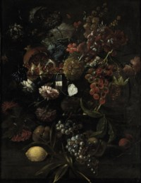 Various flowers in a glass vase with blue grapes, peaches and a lemon, all on a ledge