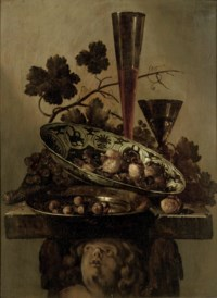 A porcelain bowl with walnuts, a pewter dish with hazelnuts and a 'Façon de Venise', all on a cherub styled pedestal