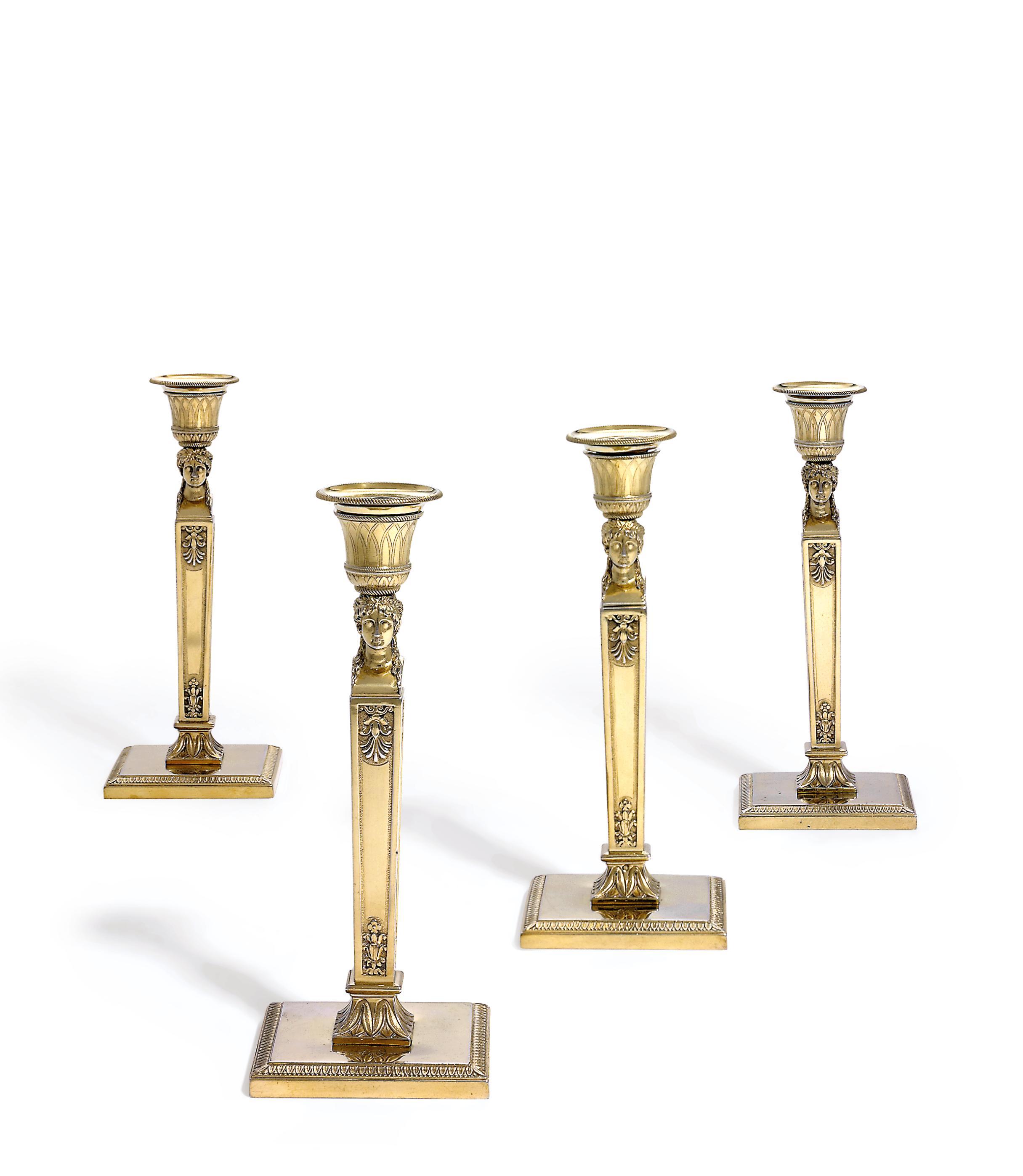 A SET OF FOUR FRENCH EMPIRE SILVER-GILT CANDLESTICKS