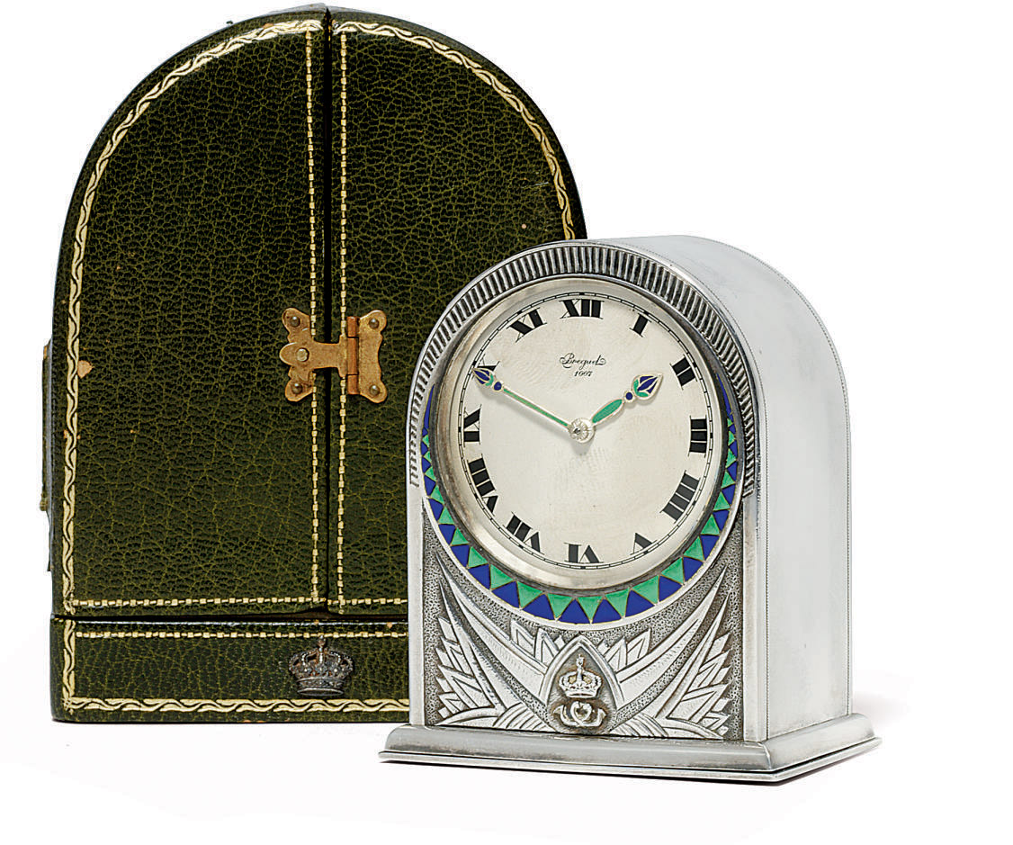 AN ART DECO ENAMEL-MOUNTED HUMP-BACKED TIMEPIECE WITH ORIGINAL BOX, BOTH WITH THE EMBLEM OF KING FOUAD I OF EGYPT