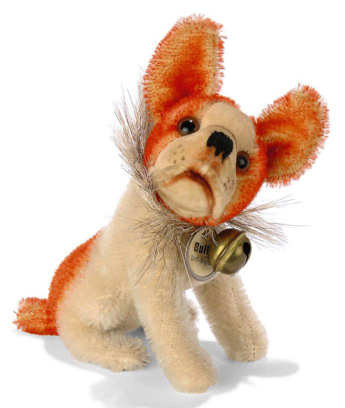 A STEIFF SEATED BULLY, (3310), white and oranged tipped mohair, brown and black glass eyes, velvet face and muzzle, black stitching, swivel head, horsehair collar with bell and white card disc with metal frame, circa 1928 --4in. (10cm.) high