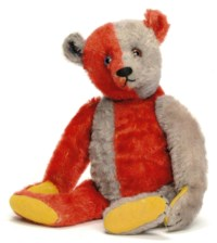 A STEIFF HARLEQUIN TEDDY BEAR, jointed, half red and half blue mohair, one blue and black and one brown and black glass eye, black stitching, yellow felt pads and FF button, circa 1925 --13½in. (34cm.) high (small bald spot below right ear, some fading mainly to the blue, blue eye cracked, patch to right pad and some general wear)
