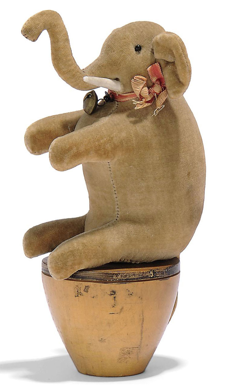 A STEIFF EARLY VELVET ELEPHANT SKITTLE, (from EleM or 4420), grey, black bead eyes, bone tusks, ribbon with bell, on turned tapering wooden base and elephant button, 1904-5 --7in. (17.5cm.) high (faded and discoloured)