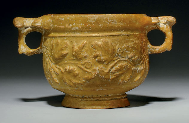 A ROMAN LEAD GLAZED POTTERY SKYPHOS