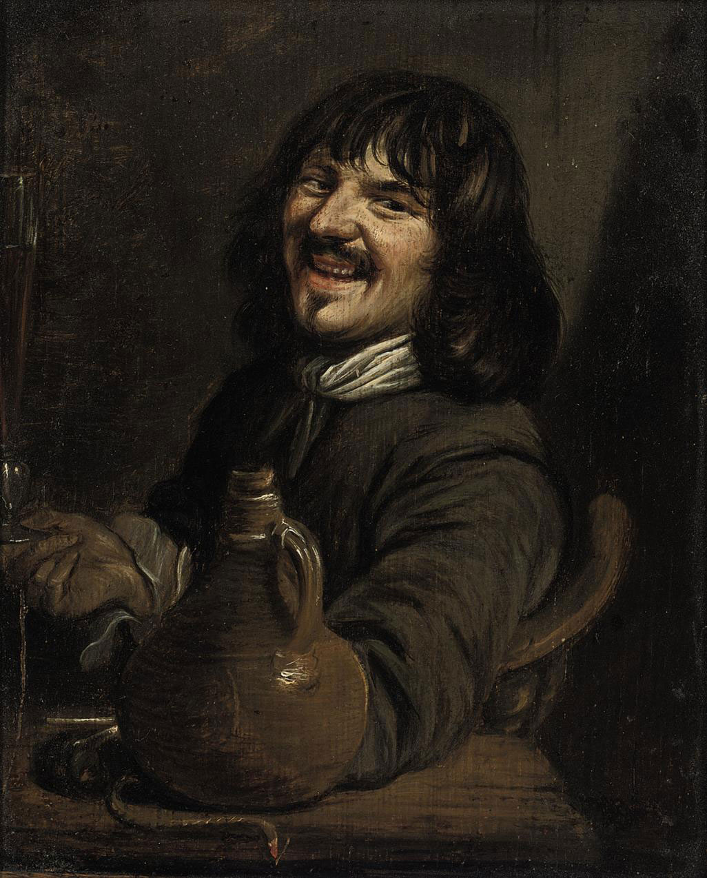 A man seated at a table drinking