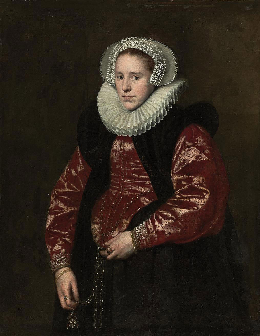 Portrait of a lady, half-length, in a lace bonnet, ruff, red gown with a black velvet mantle, holding a jewelled gold pomander