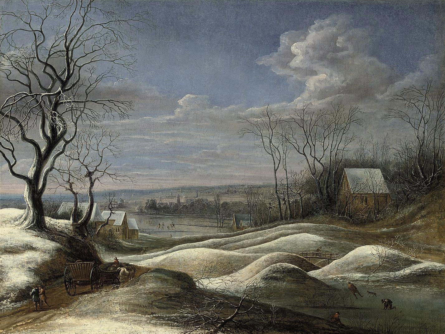 A winter landscape with travellers on a path and figures skating on a frozen lake beyond