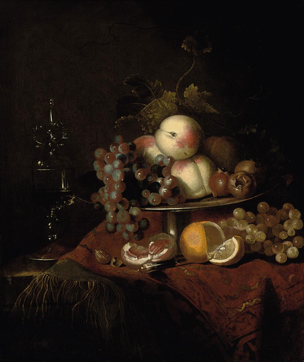 Peaches, grapes and pomegranates on a plate, a sliced orange and walnuts on a partly draped table with a wine glass
