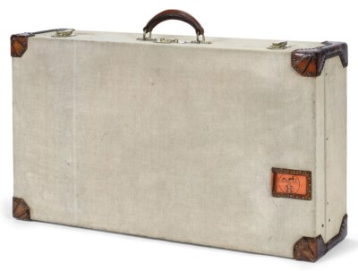 A TOILE AND LEATHER SUITCASE