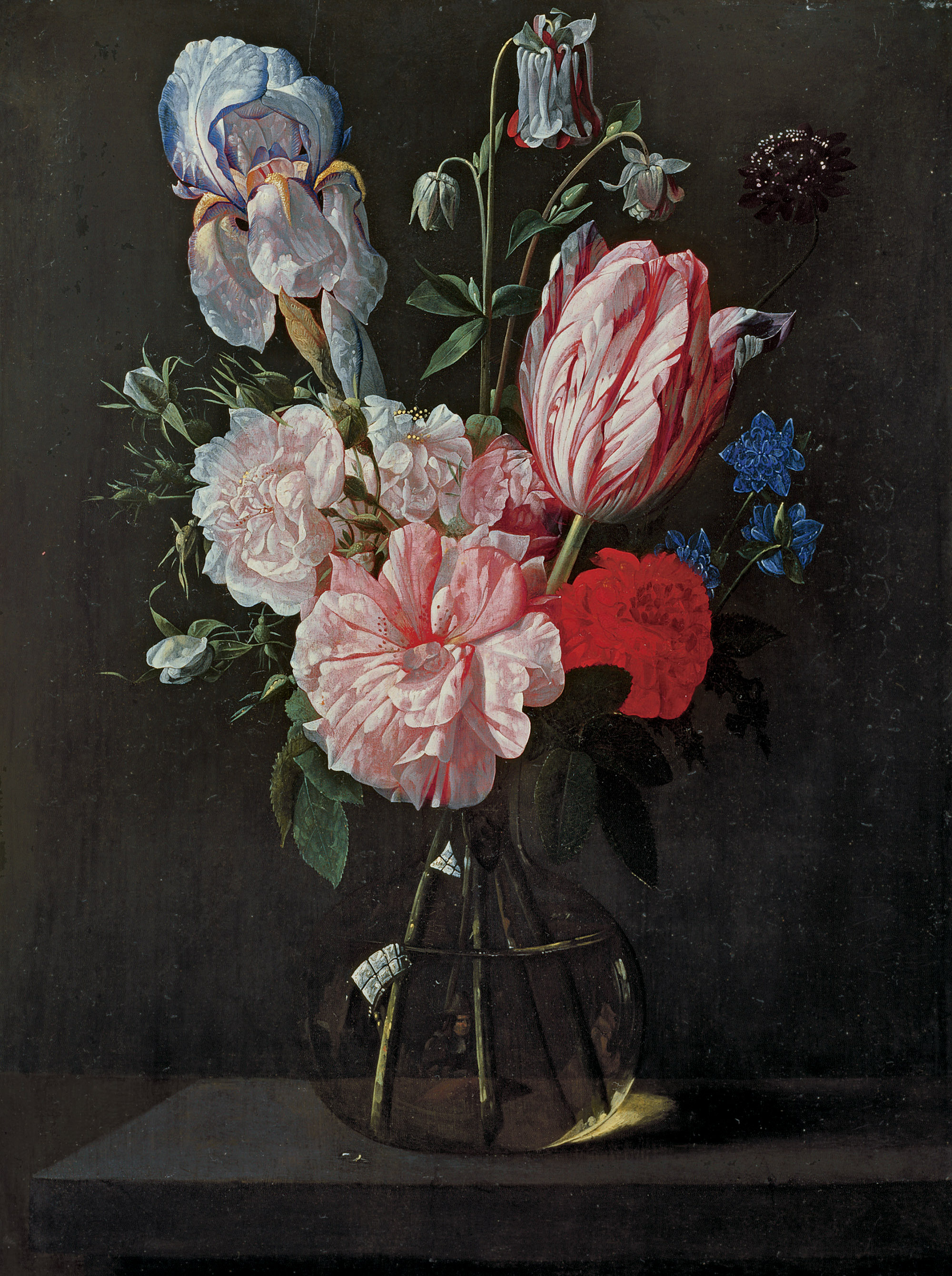 A tulip, roses, iris and other flowers in a glass vase on a ledge