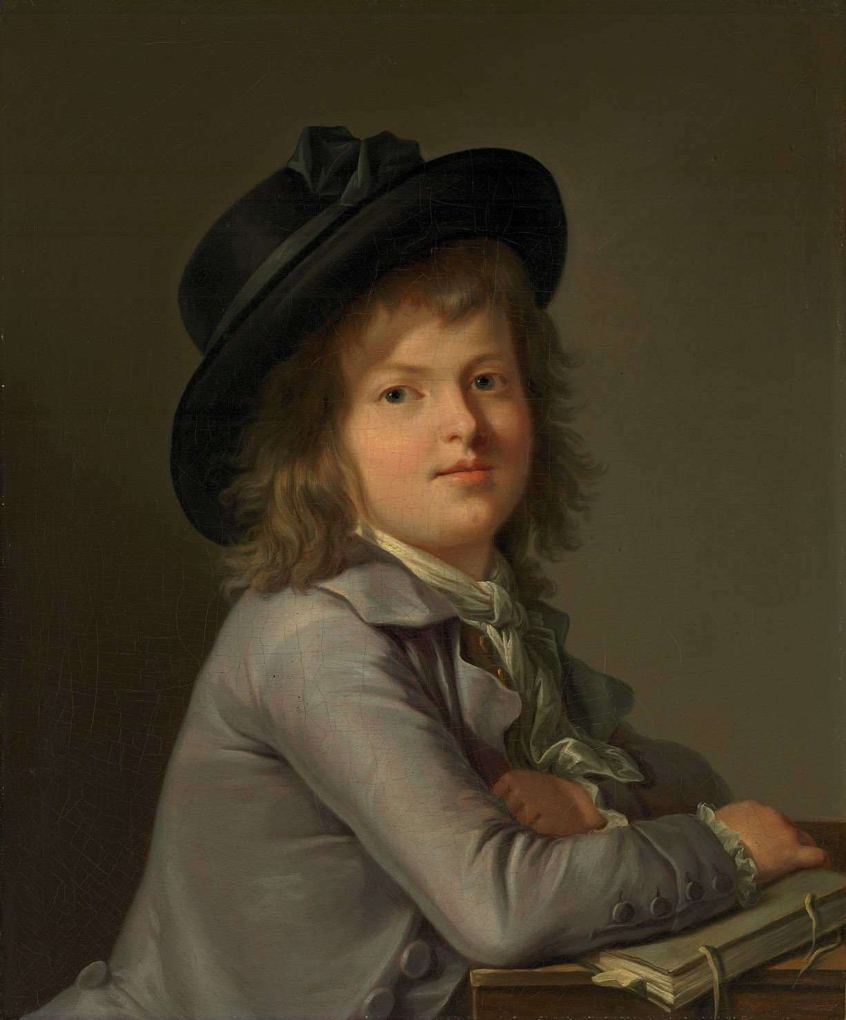 Portrait of a boy, in a black hat, leaning on a portfolio