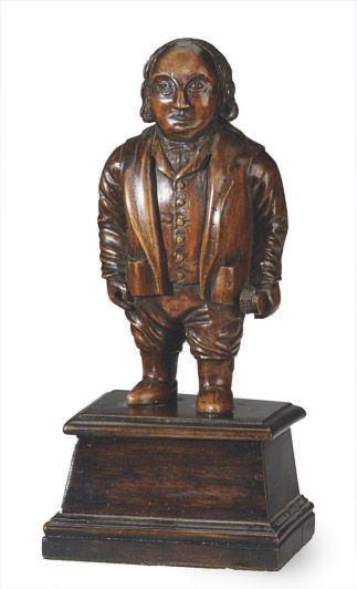 A CARVED FRUITWOOD FIGURE OF A GROOM HOLDING A BRUSH,