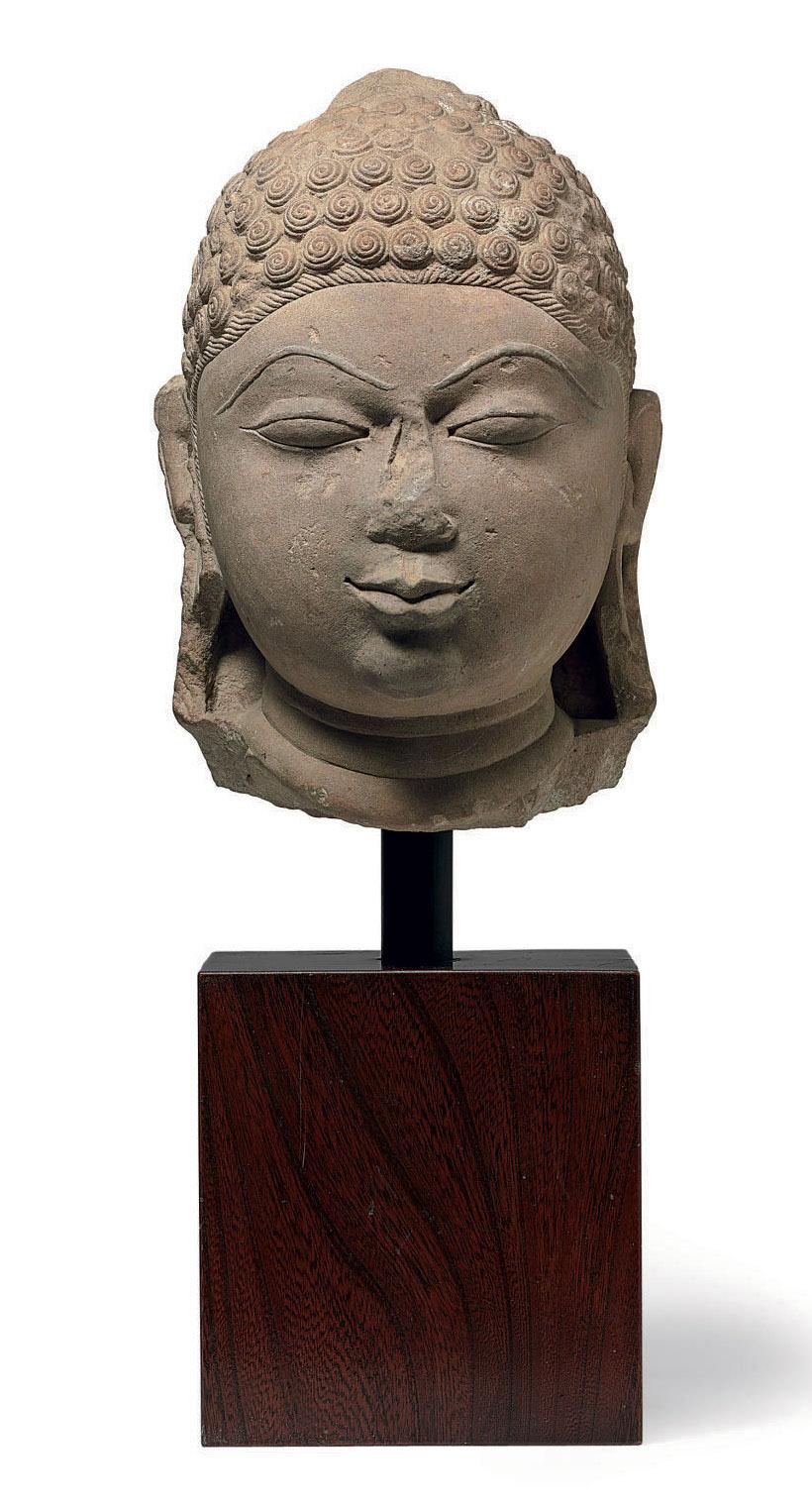 A buff sandstone head of a dei