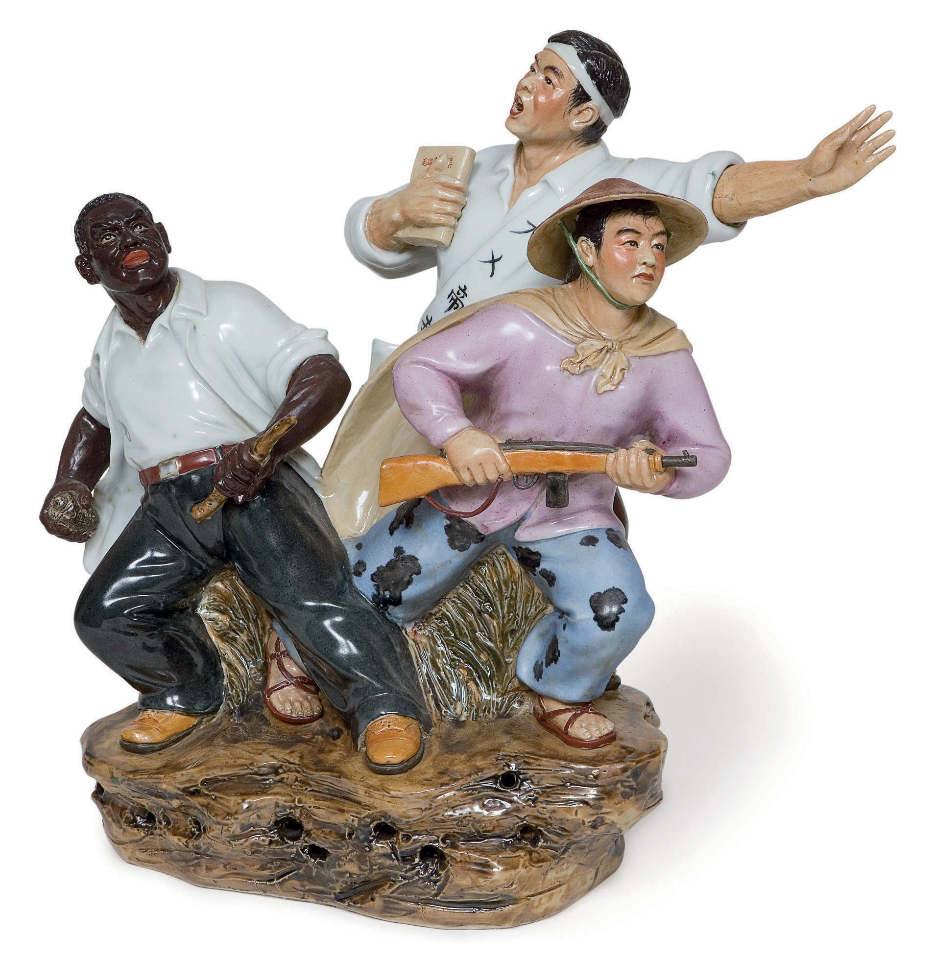 """A Fine Ceramic Group that Represents Asia, Africa and Latin America United depicting a Japanese protestor holding a copy of Mao Zedong's Selected Works and wearing a sash """"Down with Imperialism"""", with an African worker and a Vietcong soldier poiseed on a rock.  Althogether representing world unity of the proletarian people"""