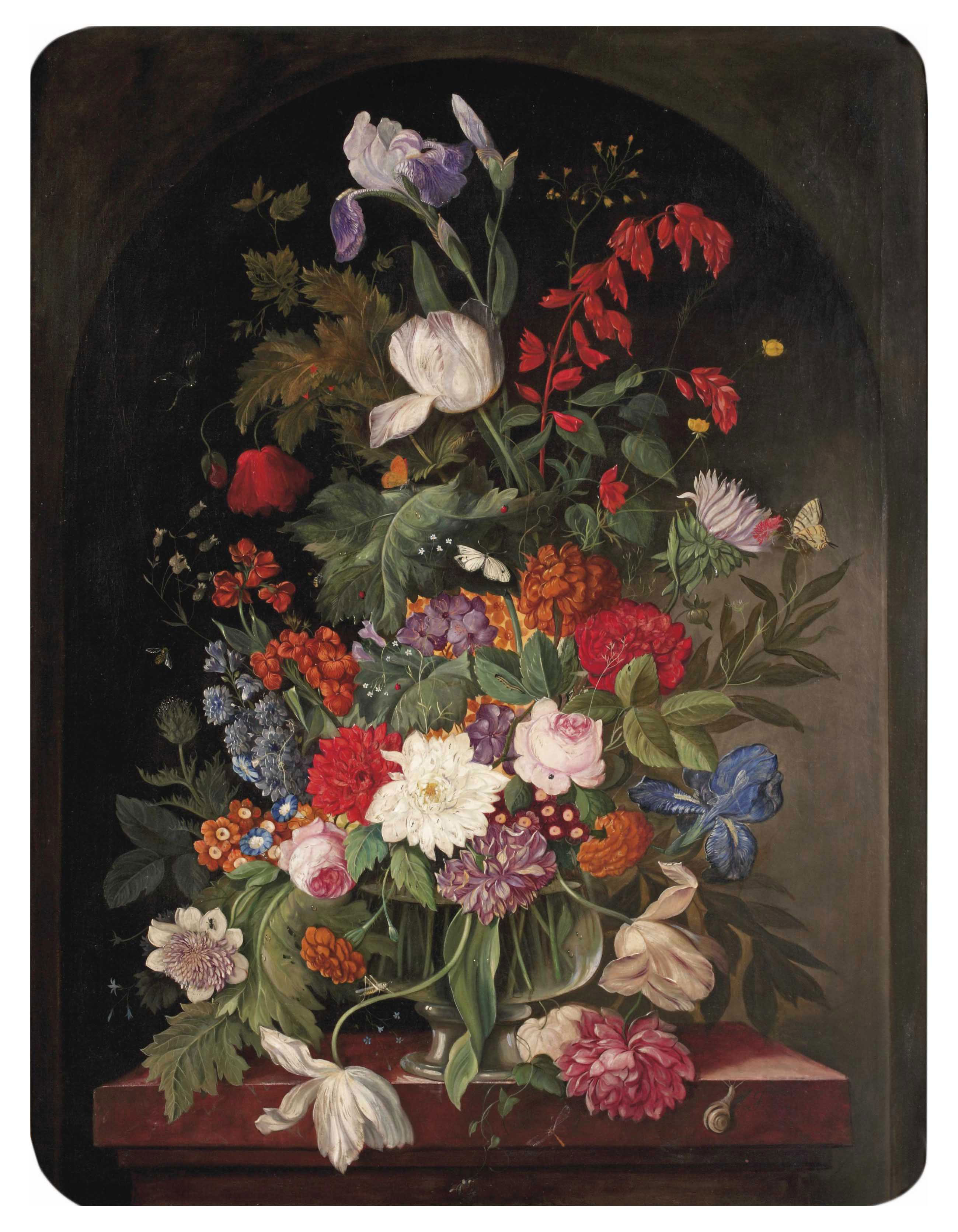 Pink roses, peonies, lilies and various other flowers in a glass vase on a marble edge in a stone ledge