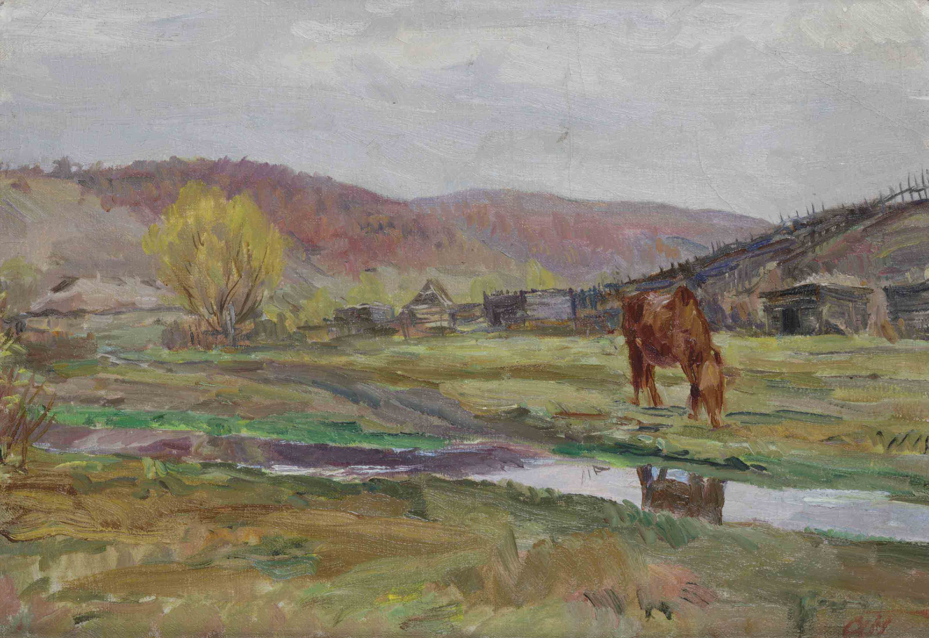 A horse grazing in a field along a river