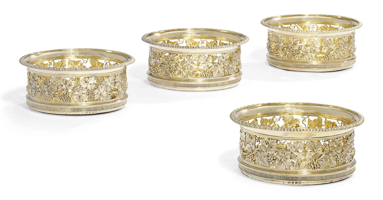 A SET OF FOUR GEORGE III SILVER-GILT WINE-COASTERS