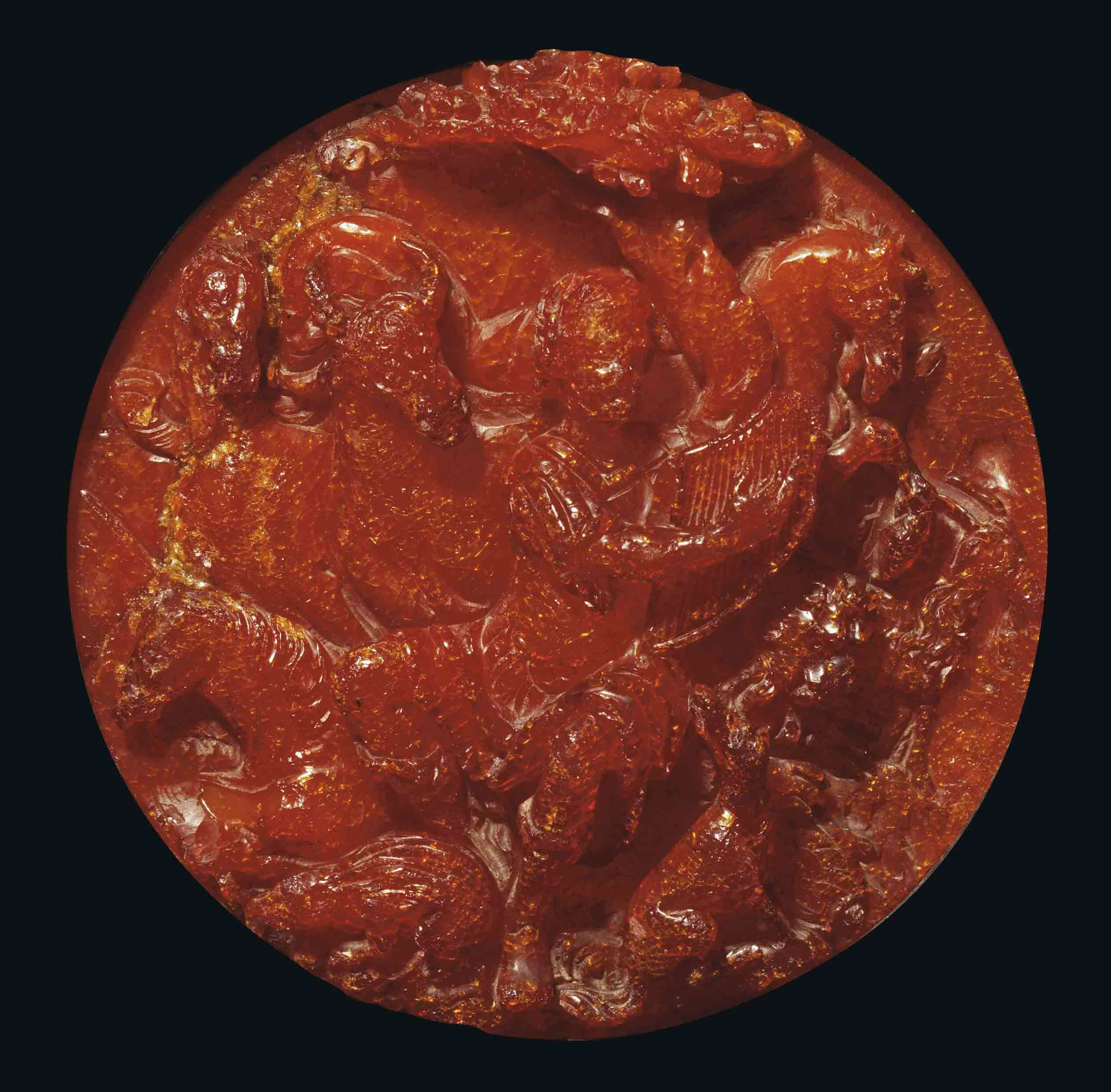 A CIRCULAR CARVED AMBER RELIEF