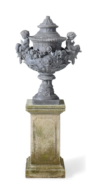 A LEAD URN ON LIMESTONE PEDEST