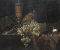 An elaborately decorated vase, a pocket watch, grapes, a carafe and a glass cup on a partially draped table