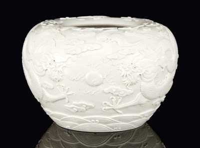 AN UNGLAZED CARVED WATER POT