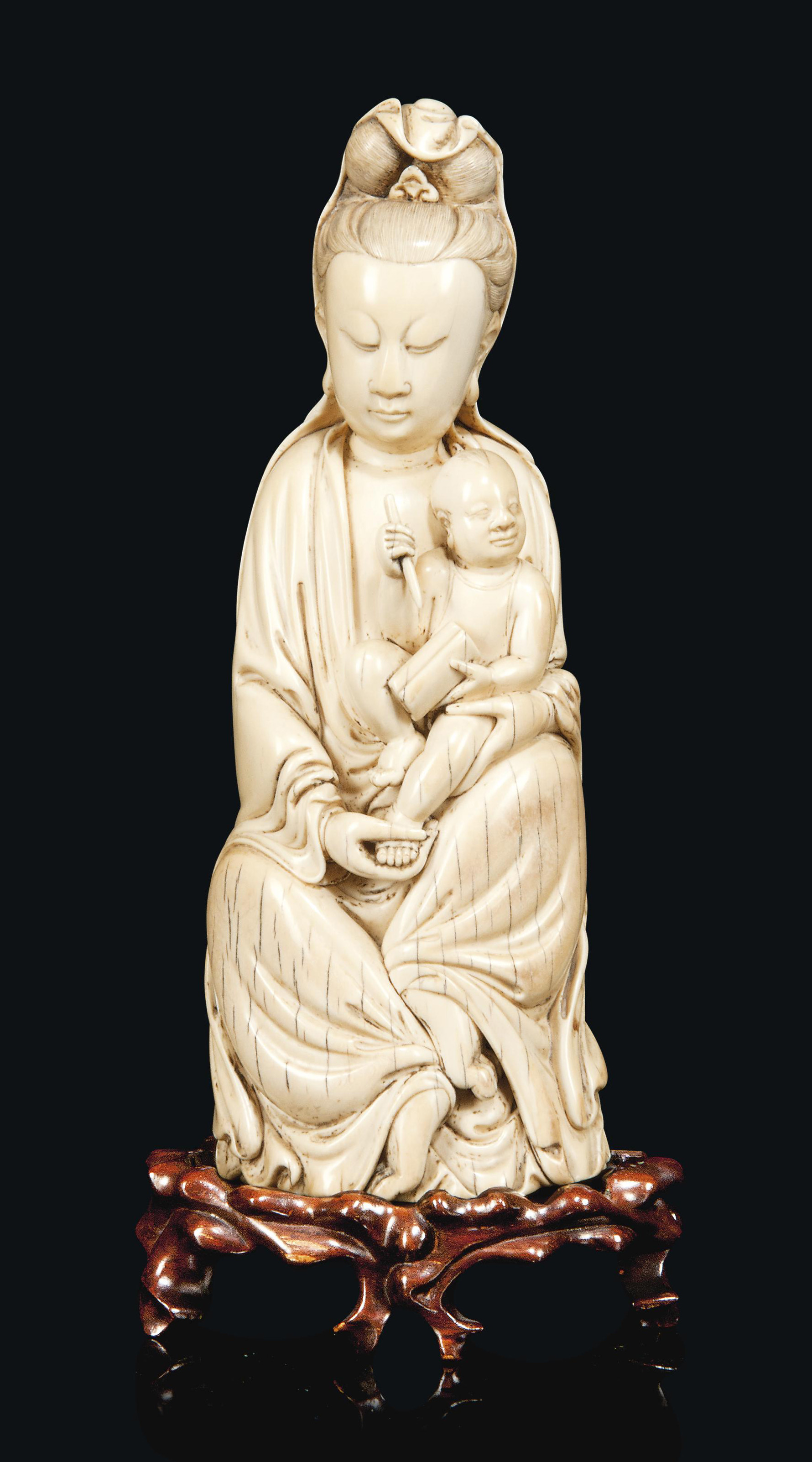 A CHINESE CARVED IVORY GUANYIN