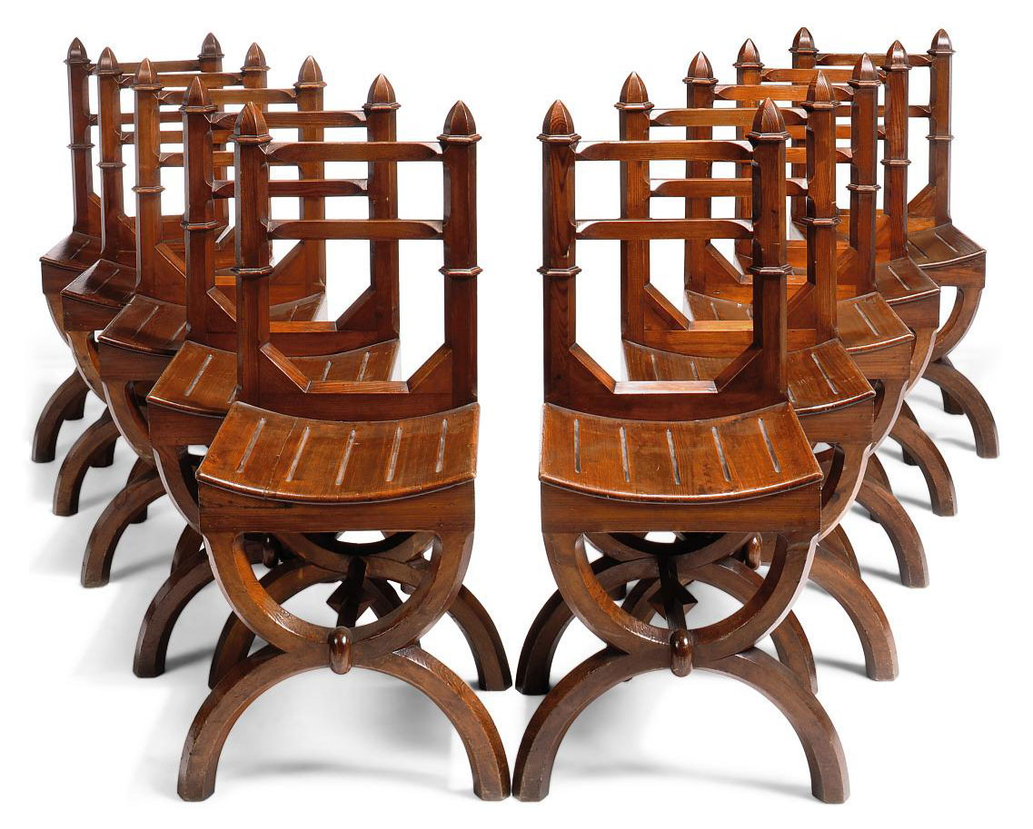 A SET OF TEN GOTHIC REVIVAL STAINED PINE DINING CHAIRS