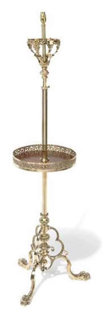 A BRASS STANDARD LAMP WITH A M