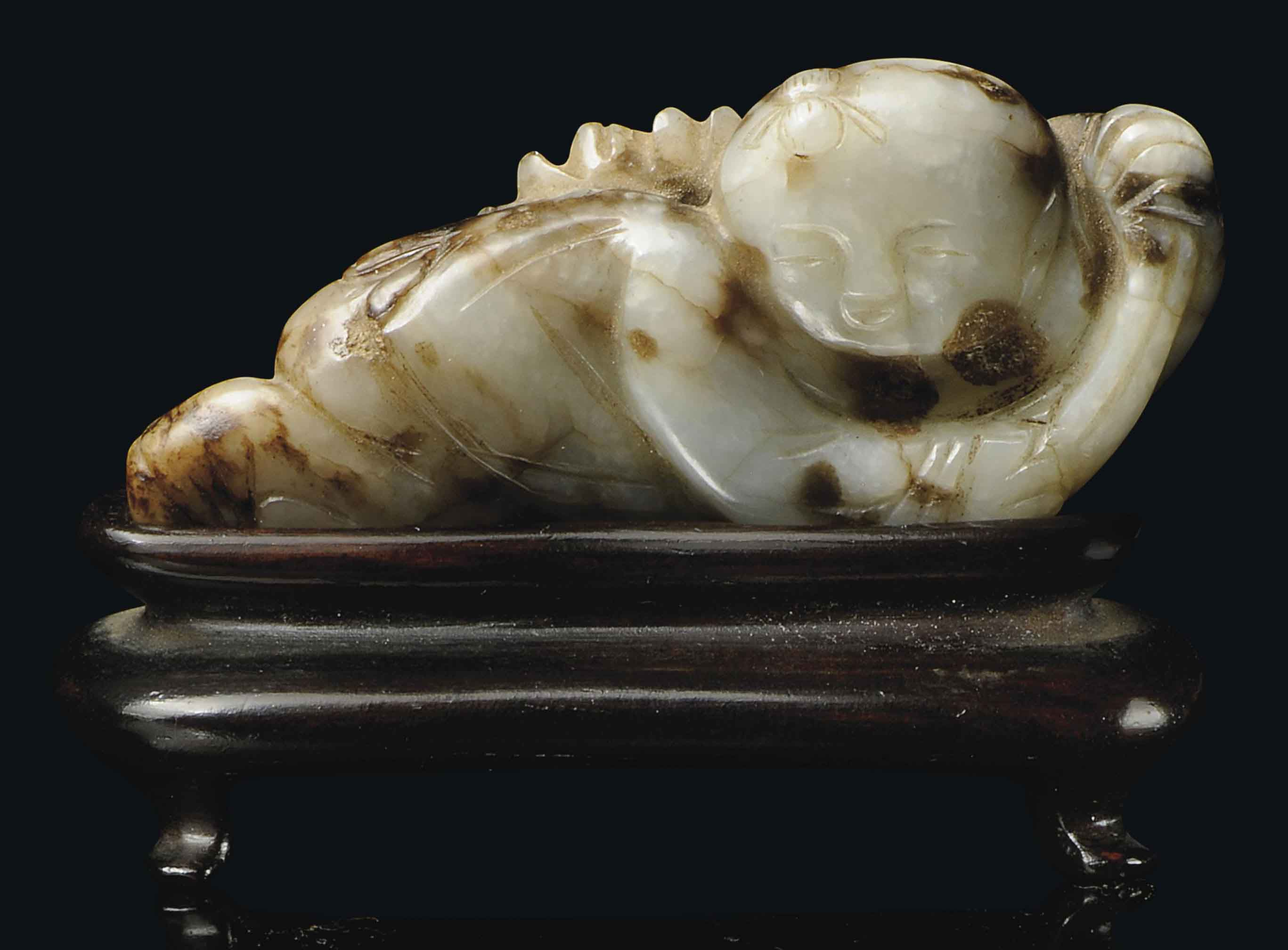 A RUSSET JADE CARVING OF A BOY