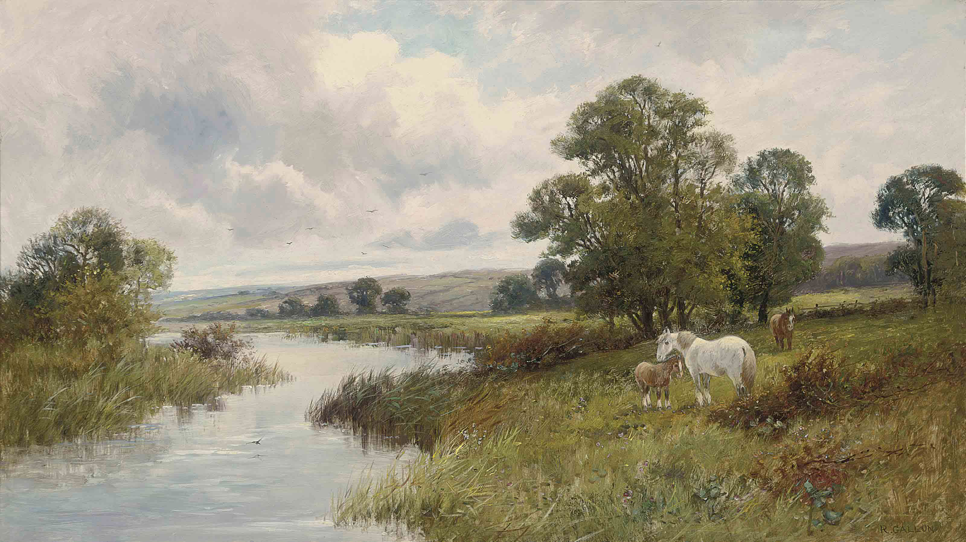 A mare and her foals grazing at the side of a river