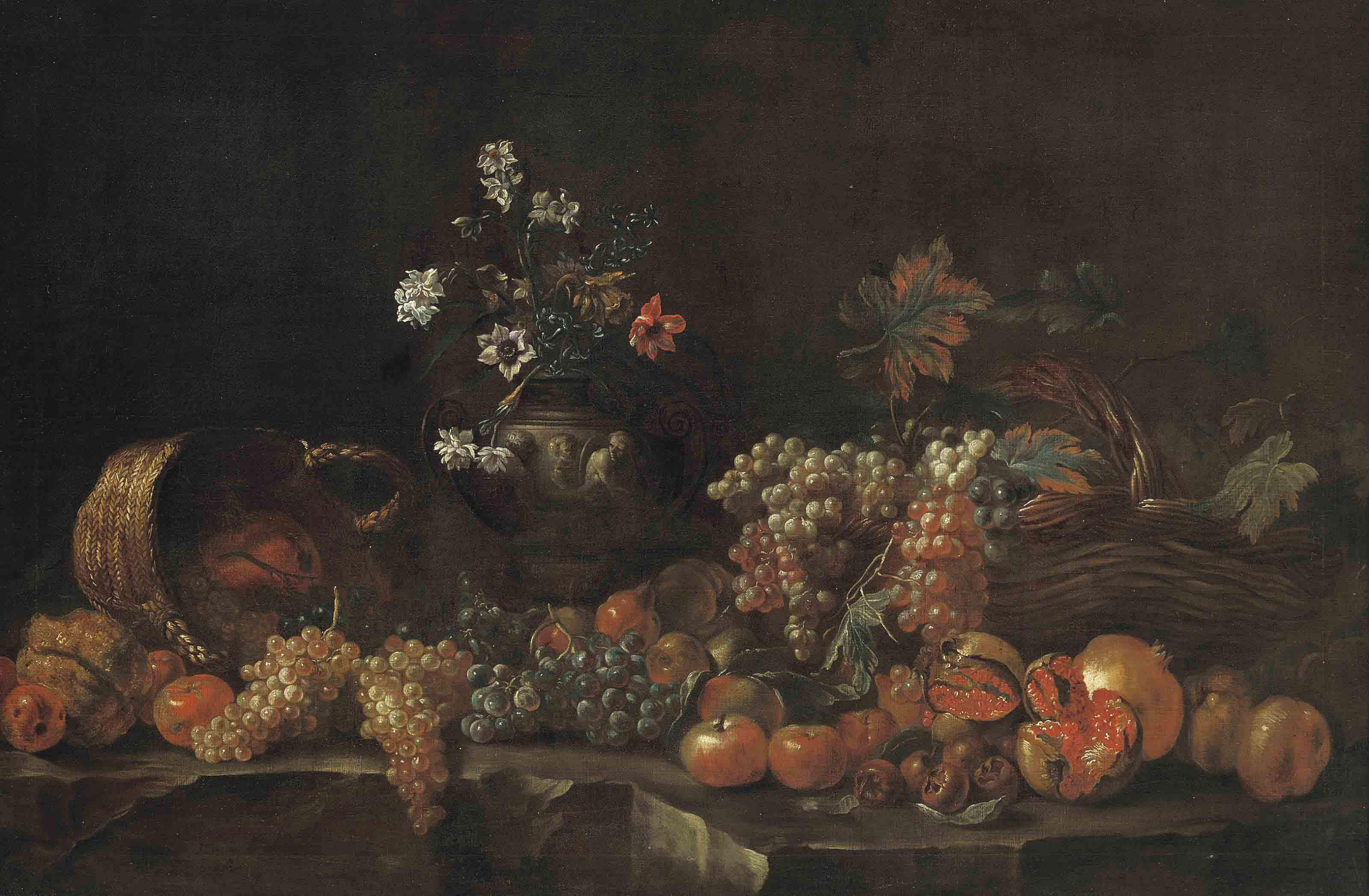 Grapes, pomegranates, apples, lemons, wicker baskets and a sculpted vase with flowers on a ledge