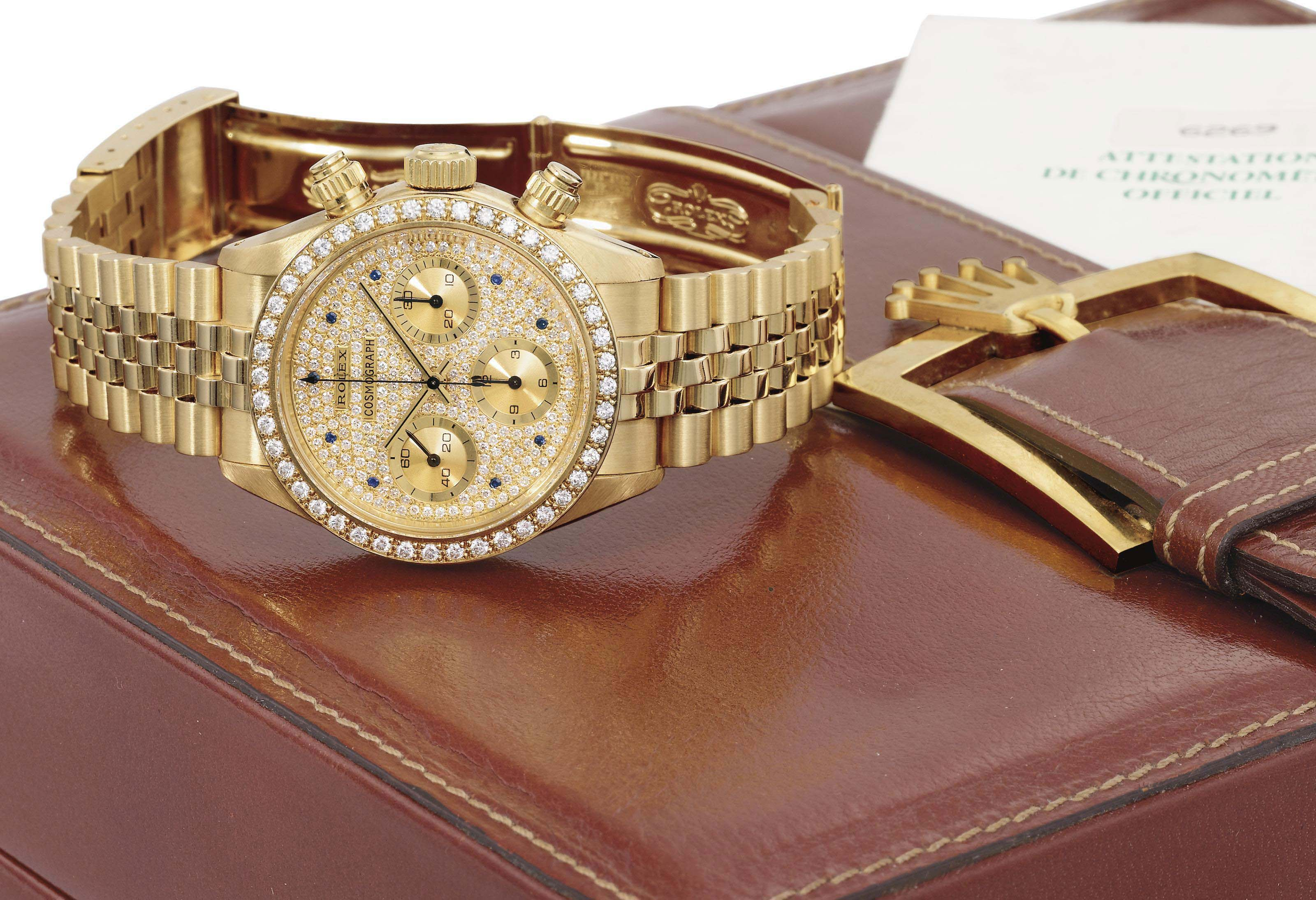 Rolex. An extremely rare and attractive 18K gold, diamond and sapphire-set chronograph wristwatch with bracelet<BR> SIGNED ROLEX, COSMOGRAPH, REF. 6269, CASE NO. 9'676'144, MANUFACTURED IN 1988<BR>