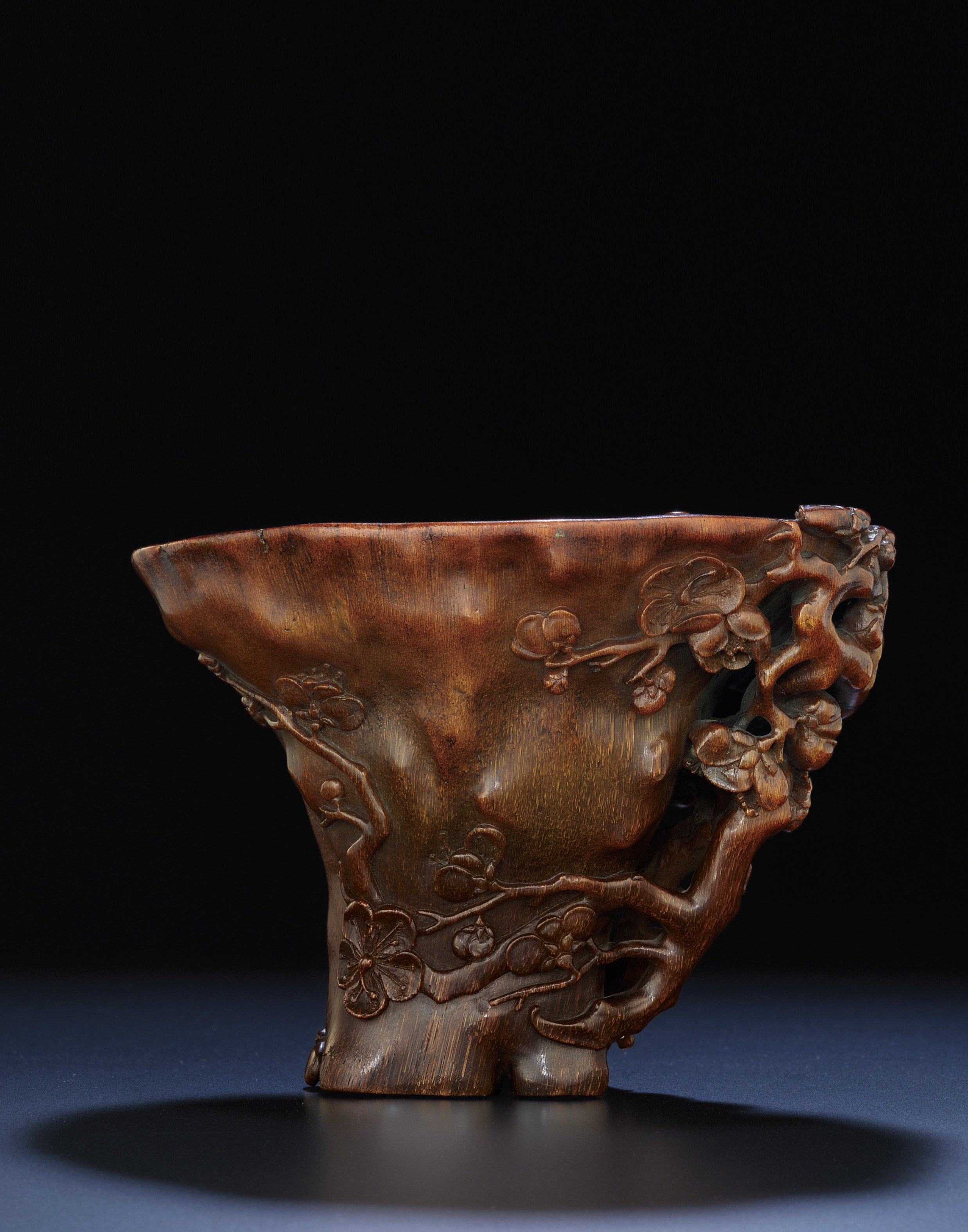 AN EXQUISITELY CARVED RHINOCEROS HORN LIBATION CUP