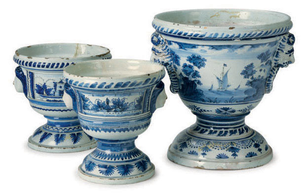 AN ASSEMBLED CONTINENTAL DELFT GARNITURE OF THREE BLUE AND WHITE LANDSCAPE-DECORATED KRATER-FORM FLOWER POTS,