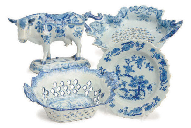 A DUTCH DELFT FLOWER-PAINTED PAW FOOTED CRUCIFORM STRAINER, A BARBED DISH, AND A MODEL OF A COW,