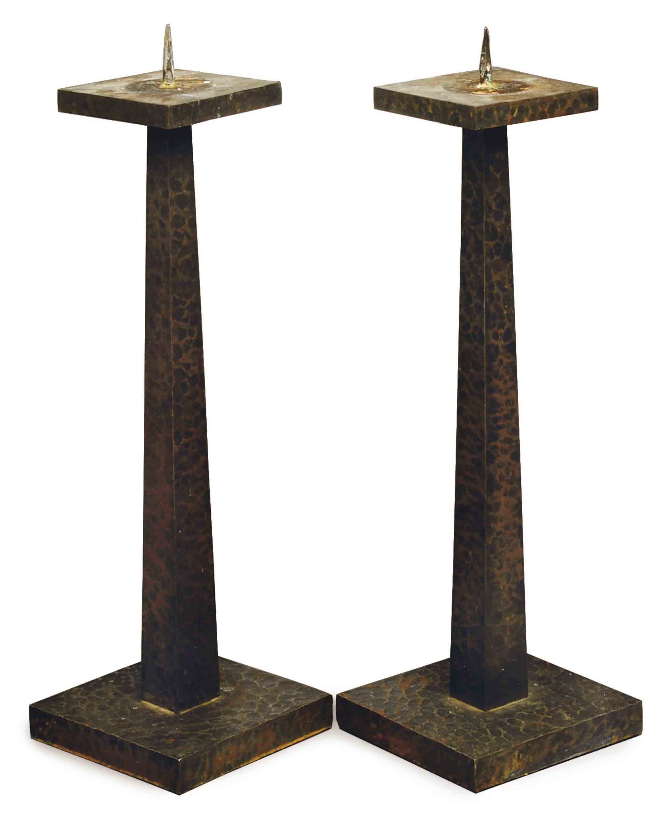 A PAIR OF ARTS AND CRAFTS HAMMERED-STEEL CANDLESTICKS,