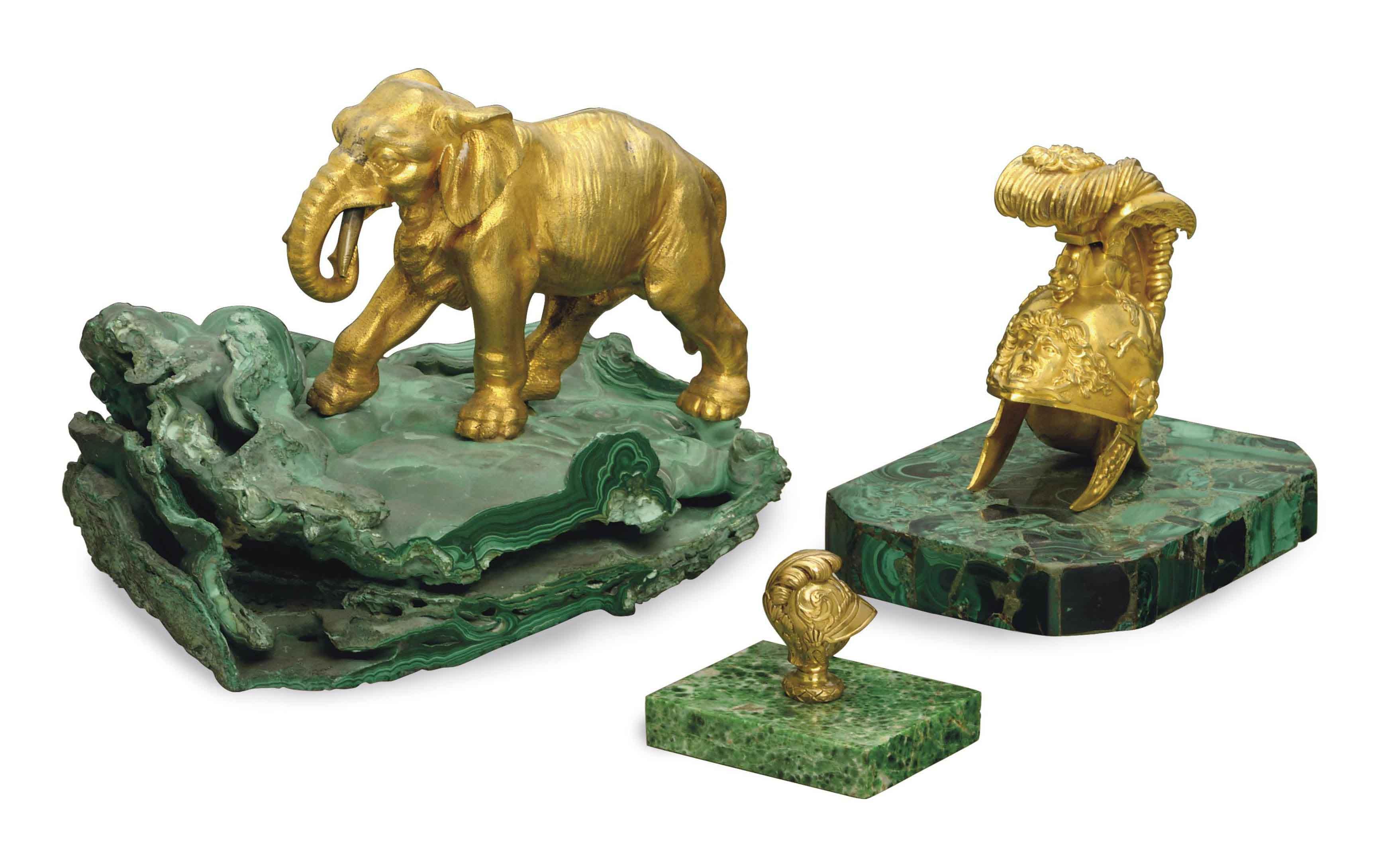 A GILT METAL ELEPHANT ON A MALACHITE BASE, A GILT METAL HELMET ON A MALACHITE VENEER BASE, AND A SMALLER GILT METAL HELMET ON A HARDSTONE BASE,