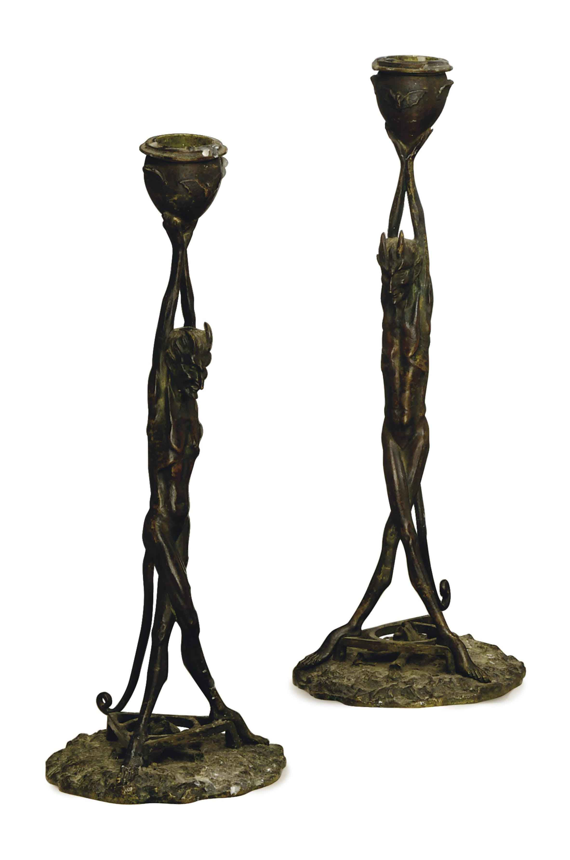 A PAIR OF CONTINENTAL PATINATED-BRONZE DEVIL FIGURAL CANDLESTICKS,