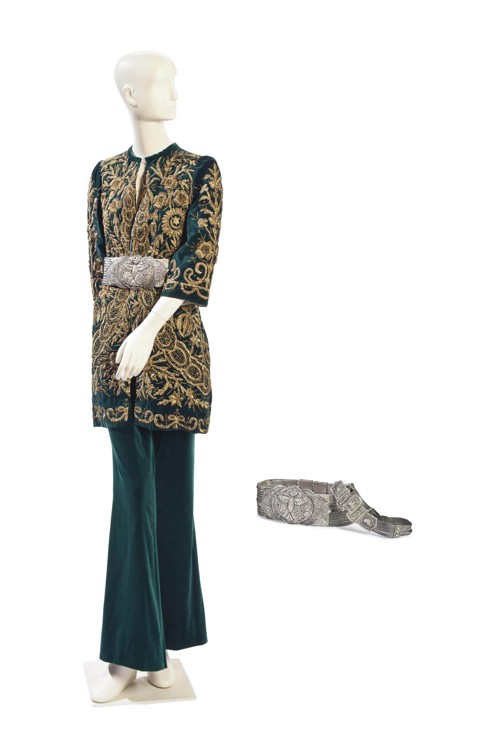 AN EVENING TROUSER SUIT OF BOTTLE GREEN VELVET WITH TWO WHITE-METAL BELTS
